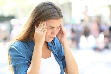 woman holding head suffering with migraine. Preston chiropractic associates can locate the source of the pain