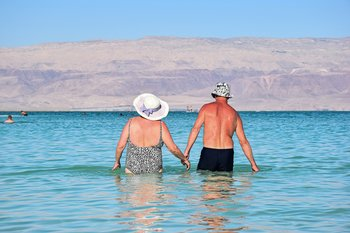 Older couple on holiday wading in the sea holding hands enjoying an active and healthy life