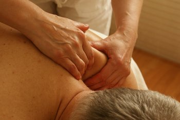 Chiropractic Associates sports therapist using manual massage on the shoulder of a male patient